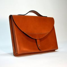 Elegant and durable leather document case made of vegetable-tanned leather in cognac shade.  Functionality, classic style and durability  Elegant case for documents and handy items such as tablet or small laptop. Hand-crafted of vegetable-tanned leather*/hydrophobic leather, perfect for