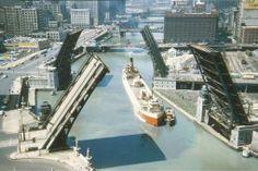Laker and tug, Chicago River, bridges up, 1950s