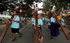 Women carry crosses in East Timor. | 16 Ways To Celebrate Holy Week Around The World