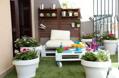faux grass carpet and white painted pallet furniture