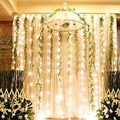 Create your own magical woodsy lamp backdrop with strings of lights mixed with garlands of greenery.