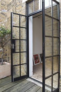 Double metal French doors from kitchen to garden. • Via Bodie and Fou.