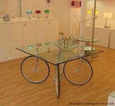 Mesa... sendo utilizadas rodas de bicicletas e tampo de vidro.
