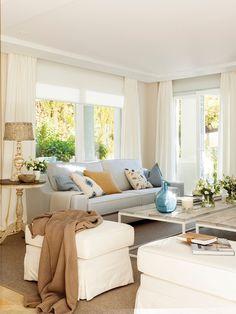 Salón con sofá gris piedra, mesas de centro de madera blanqueada y metal, puf blanco, plaid, grandes ventanales y damajuanas en azul