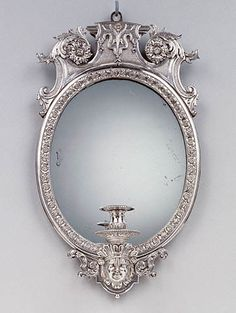 "1700 French/Swedish Wall light (one of two) at the J. Paul Getty Museum, Los Angeles - From the curators' comments: ""Acanthus leaves, a mask, and rosettes, all typical motifs of the late Baroque period, decorate this pair of oval mirrors. The mirror glass reflected the flames of the candles held in the holders, thereby increasing the amount of light produced. Small mirrored wall lights, consisting of one branch each, would probably have hung in a bedroom or study of a private townhouse."""