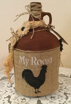 Upcycled gallon jug with stenciled rooster on burlap. Burlap flowers, metal key and cheesecloth complete this faux rusty jug. Wipe gently with damp cloth to clean. Thanks for visiting and keep checking for new listings. Wine Jug Crafts, Liquor Bottle Crafts, Mason Jar Crafts, Wine Bottles, Glass Bottles, Burlap Projects, Burlap Crafts, Jar Art, Glass Jug