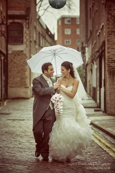 Bride and groom walking in the rain on a cobbled street with a white umbrella on their wedding day.