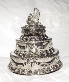 Stunning silver plated wedding cake! It's made by International Silver Co. It's three tiers of cake adorned with silver roses and garland on each tier. It's topped off with a couple of wedding doves. The top lifts off at the second tier to reveal red velvet lining inside. It also has red velvet on the bottom