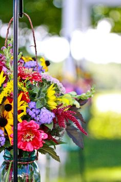 Wildflower Wedding Decor- aisle bouquets in mason jars with vibrant meadow color palette