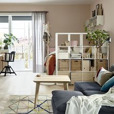 Living in a small space? Use a shelving unit like KALLAX to create a divider that separates your sleeping space from your living room!