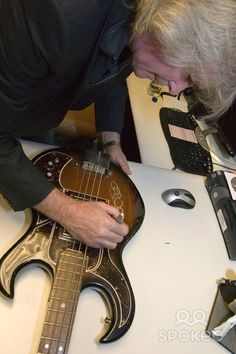 Cliff Williams signing his guitar The Hard Rock unveils a new display case to honour of Cliff Williams of AC/DC