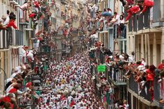 Pin for Later: The Most Compelling Pictures of 2014  The streets of Pamplona, Spain, were packed with revellers who ran with the bulls for the annual Running of the Bulls festival.