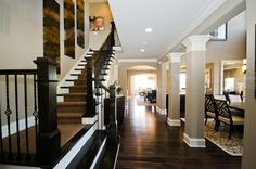 Dark wood on the stairs and taupe pillars trimmed in white define this open hallway.