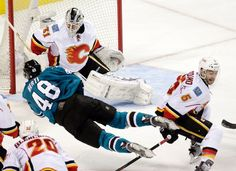 San Jose Sharks forward Tomas Hertl fires a shot on goal as he is tripped up by Calgary Flames defenseman Mark Giordano (Nov. 26, 2014).
