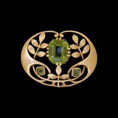MURRLE BENNETT & Co. (1896-1914)  A gold brooch set central peridot and accented with two rectangular peridots.   Anglo/German c.1900. Marks for MB & Co. and 15 ct.  Size: Height 2 cm. Width 2.6 cm. (Brooch case)   Lit.: Art Nouveau Jewelry. Vivienne Becker. Liberty Style. Academy Editions.