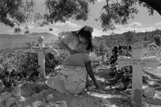 Larry Towell  EL SALVADOR. San Salvador. 1991. A daughter comforts her mother who passed out while grieving at the grave of her son who was killed by government death squads. Some 70,000 persons died in the 12-year civil war.