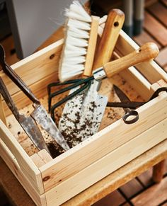 A wooden box is filled with gardening tools.