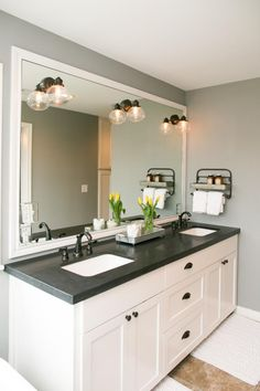 The newly added master bath has black granite countertops, soft gray walls, white cabinets and double vanity, as seen on HGTV's Fixer Upper.