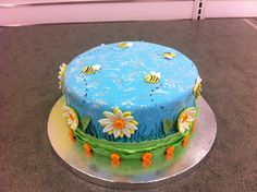 Course 3 skills - Fondant covered cake with gum paste daisies and bees, painted sky and grass on sides of cake.