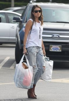 105aec37aade Celebrity Street Style Picture Description A graphic tank and leather boots  worn with your boyfriend jeans make for the perfect put-together day-time