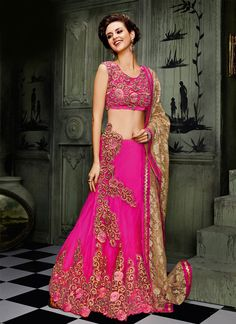Grab the second look in this elegant attire for this season. Make the heads flip after you costume up in this enticing hot pink net a line lehenga choli. The incredible attire creates a dramatic canva...