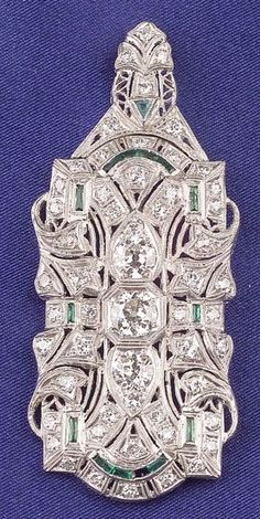 Art Deco Platinum and Diamond Pendant/Brooch, bead-set with fifty-five old European and transitional-cut diamonds, approx. total wt. 2.99 cts., green stone highlights, millegrain accents, lg. 2 3/8 in.
