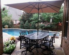 "Treasure Garden's 8' x 10' umbrella shading a 42"" x 86"" Grand Terrace oval dining table and swivel dining chairs by Gensun Casual Yard of the Month - July - Yard Art Patio & Fireplace"