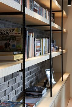 Rebar and wood bookshelves over an exposed brick accent wall enhance the…