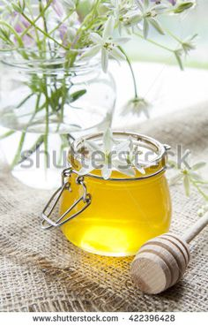Honey in jar and white flowers on table