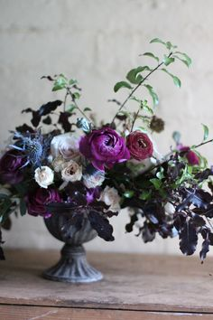 Floral table arrangement by a student (Pei)at a Jennifer Pinder Floristry workshop. Jennifer Pinder is based in Kent and specialises in wedding flowers and holding classes for both hobbyists and both professional florists. This arrangement has gorgeous deep purples, with touches of blue, plum, and the palest of blush pinks. The flowers used include ranunculus, roses, thistles and scabious seed heads. Foliage was foraged from her garden and the wedding table arrangements sits in a dark grey…