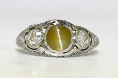 Cabochon Cat's Eye with old mine and round diamond accents. See this platinum antique engagement ring in our estate jewelry store in Santa Barbara, CA.