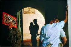 Photo by Alex Webb. This photo has everything the colours, shadows and contrast are all inspiring, the man shielding the sun with a book and the lovers highlighted. The sillouette of a man with a child is perfectly framed by the arch.
