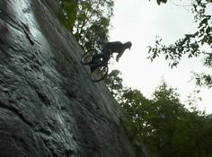 Bicycle abseiling down vertical cliff.