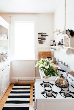 Small kitchen with open shelving and black and white stripe runner rug. // Photo by Colin Price