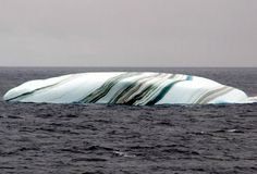 In this remarkable capture we see a multicolored striped iceberg spotted somewhere near Antarctica, about 2,700 km south of Cape Town, South Africa. This image along with a series of other amazing photos of icebergs and glaciers were the subject of popular email forwards many years back, often incorrectly labeled as icebergs in Lake Michigan or Huron.   While the location was incorrect, the phenomenon is indeed very real.