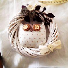 Corona di benvenuto colata nel bianco opaco decorata con gufo e rose di stoffa grezza