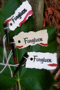 "masonry nails, dipped in red paint, with ""forgiven"" tags"