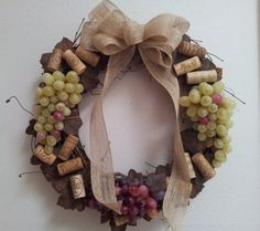 Great wreath for the wine-lover in your family! This grapevine wreath is decorated with assorted wine corks, silk grapevine leaves, two bunches of white grapes, and one bunch of red/purple grapes. The wreath is accented with a natural fiber bow. This wreath would look great on a door or hanging in a kitchen or bar area! The width of the wreath is approximately 14.