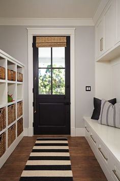 Gorgeous monochrome entryway. Plenty of storage with those cube shelves and the drawers in the bench. I need that striped rug!