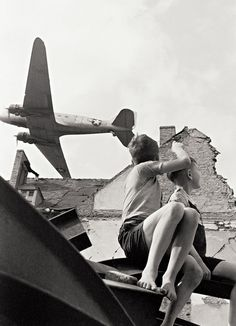German children playing in the rubble of Berlin watch an American C47 fly overhead during the Berlin Airlift, 1949.