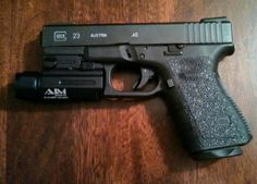 Glock 23 with AIM Sports tactical light, Vickers mag plate,Tractiongrips, and Truglo night sights.