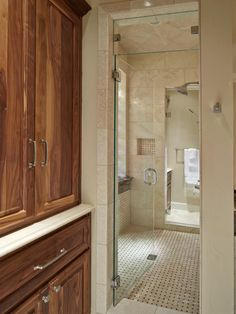 Rich tones of beige and natural wood create a bright and comfortable bathroom. The large walk-in shower is wonderfully spacious and filled with natural light. Basket-weave tile floors are a unique point of interest.