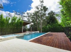 Beautiful luxury backyard with infinity pool and spa. The mahogany wood deck meets against porcelain tiles to create an attractive patio area.