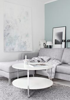 You'll want to cozy up and spend the day with a good book and a cup of your favorite Grand Cru in this gorgeous gray-hued living room. A pop of tranquil blue on one wall gives the space some visual interest amongst the neutral tones.