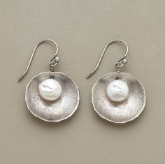 "Freshwater cultured coin pearls nestle inside flat ""shells"" of brushed, oxidized sterling silver, suspended from silver French wires. Pearls may vary in size and color. Imported. Exclusive. 1""L."