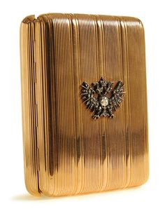 A FABERGE GOLD AND DIAMOND SET CIGARETTE CASE August Hollming, St. Petersburg 1899-1908.  The ribbed body set with Imperial Eagle embellished with diamonds and with cabochon sapphire thumbpiece.  $21,240.00