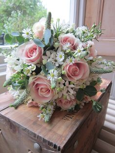 Pale pink ' sweet avalanche'  roses with white bouvardia , white veronicas , daisies and silver eucalyptus