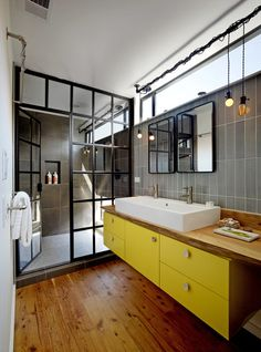 Industrial Bathroom by Berkeley Architects & Building Designers Robert Nebolon Architects. The black 'grid' frames the shower cabin. The mirrors and the mounting for the lamps give the bathroom industrial touch that contrats the yellow and the warmth of the wood.