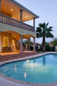 Canterra stone columns and balustrades on the verandas overlooking the pool give the home a Tuscan look.