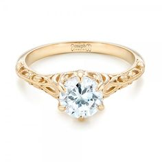 * in platinum #102767 This elegant engagement ring features a round brilliant cut diamond in a six prong yellow gold setting with custom filigree and milgrain accents on...